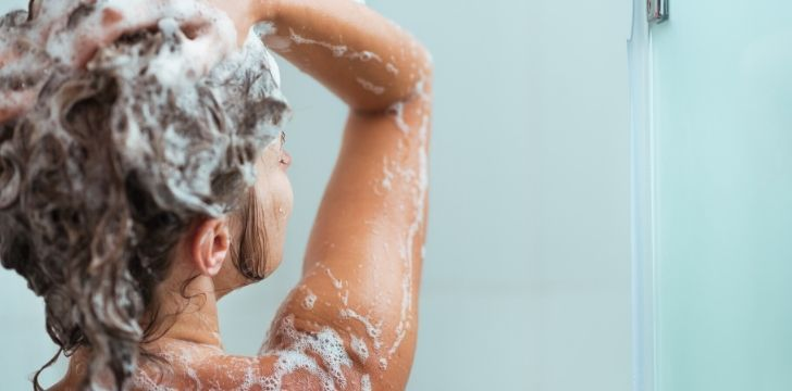 A woman using shampoo in her hair in the shower