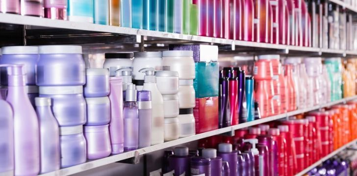 Many bottles of shampoo on shelves at a store